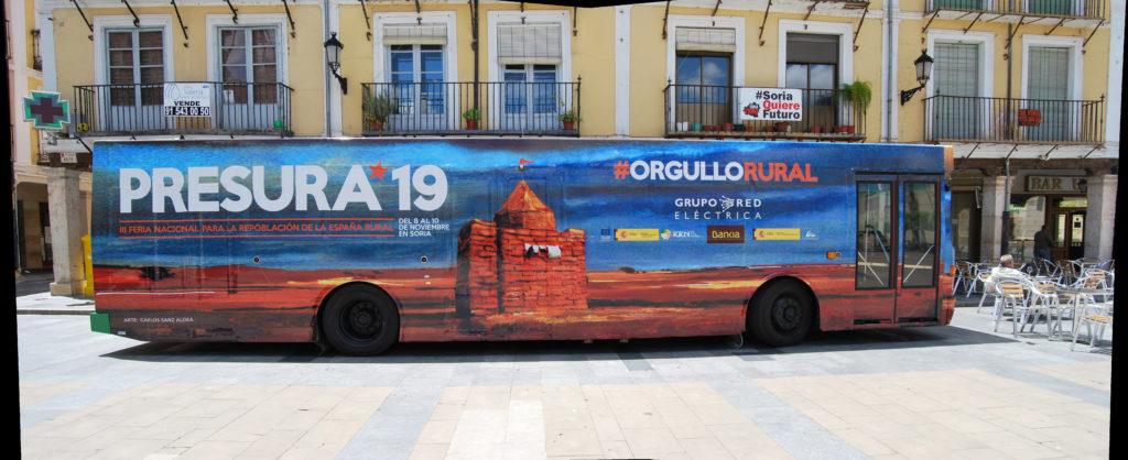 El autobús de Presura, en la plaza Mayor de El Burgo, el lugar en el que se estrenó el vehículo.